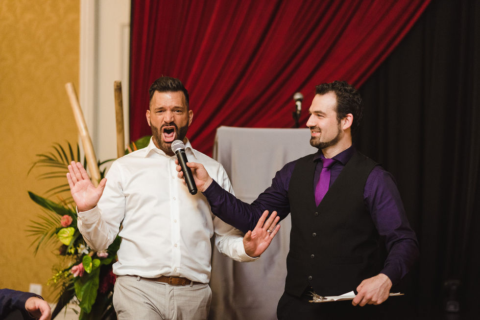 wedding MC holding microphone up to a wedding guest that has his hands up and is yelling during reception at the Hilton Fallsview in Niagara Falls