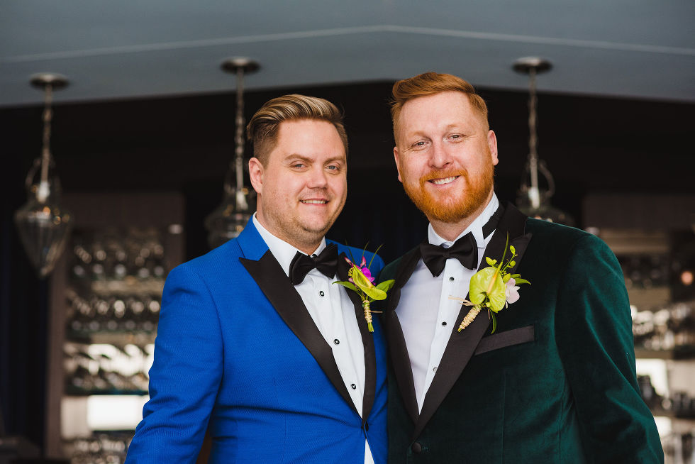 Grooms smiling and standing side by side before their wedding at the Hilton hotel in Niagara Falls