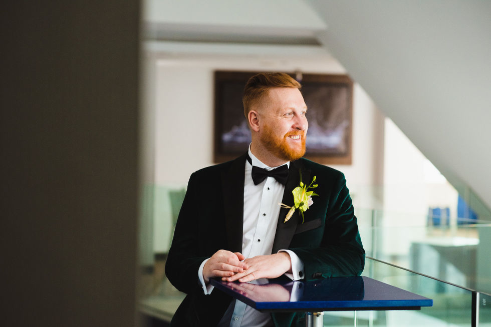 groom in green suit smiling and standing at a bar table before his wedding at the Hilton hotel in Niagara Falls