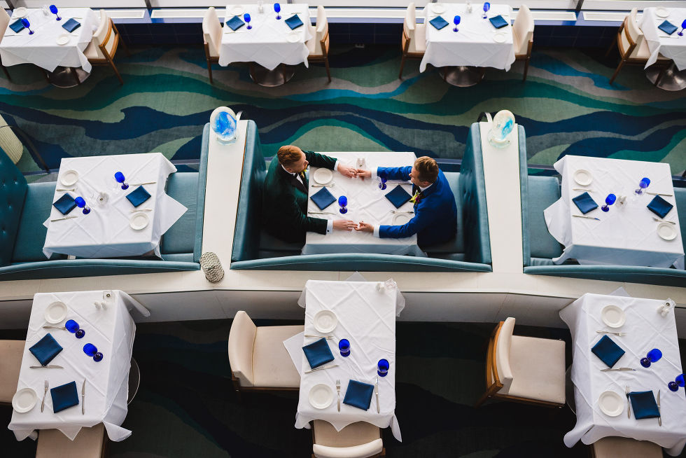 aerial shot of grooms holding hands across the table while sitting in a booth in the Hilton hotel in Niagara Falls before their wedding ceremony