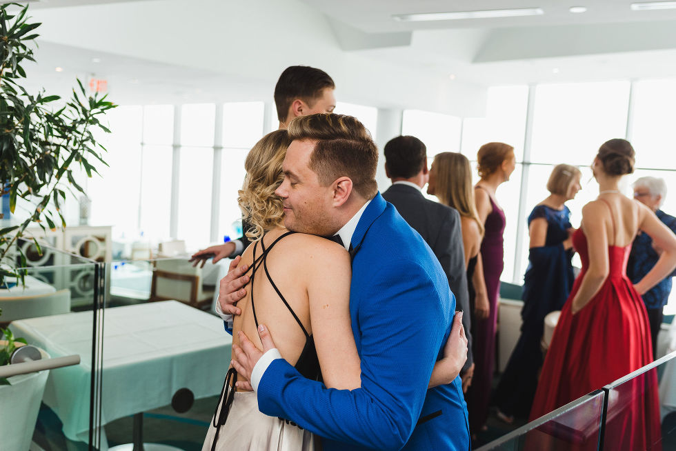 groom in bright blue suit hugging a wedding guest at Hilton Niagara Falls