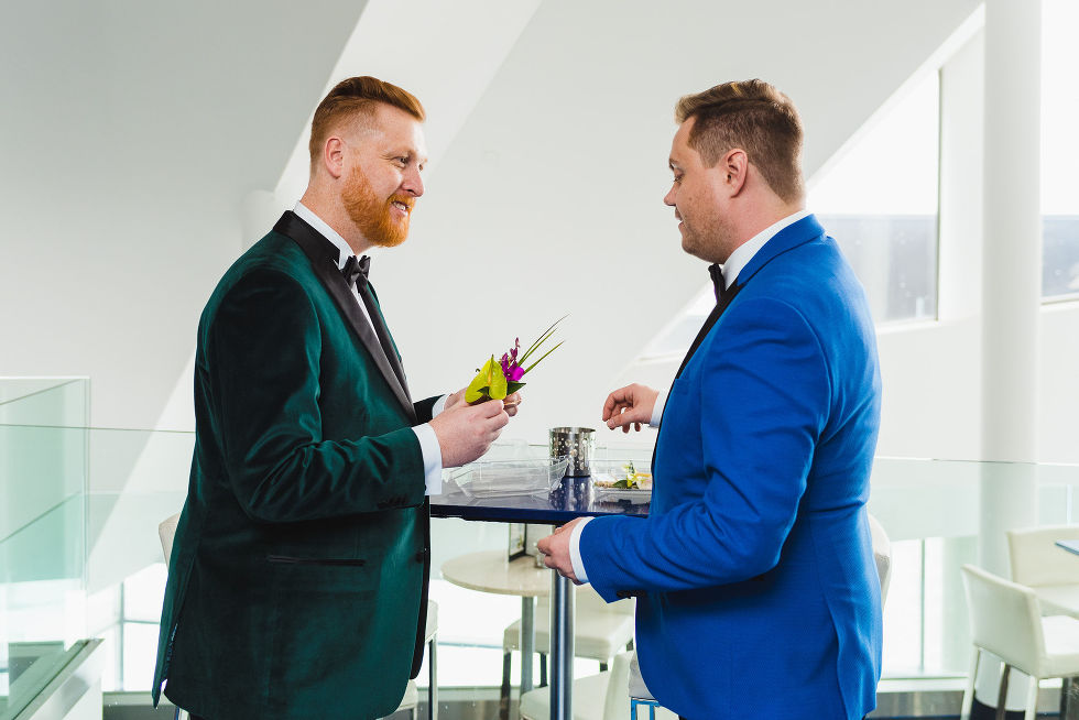 groom in a green suit holding boutonniere in front of groom in bright blue suit before wedding ceremony at the Hilton in Niagara Falls