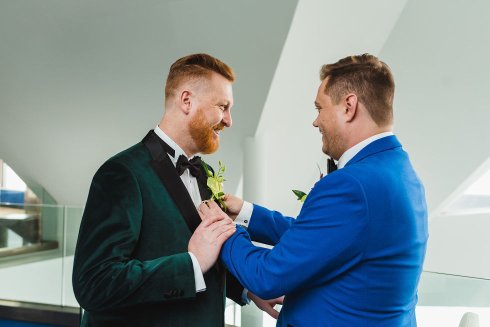 Groom in blue suit placing boutonniere on lapel of groom in green suit before their wedding at the Hilton in Niagara Falls