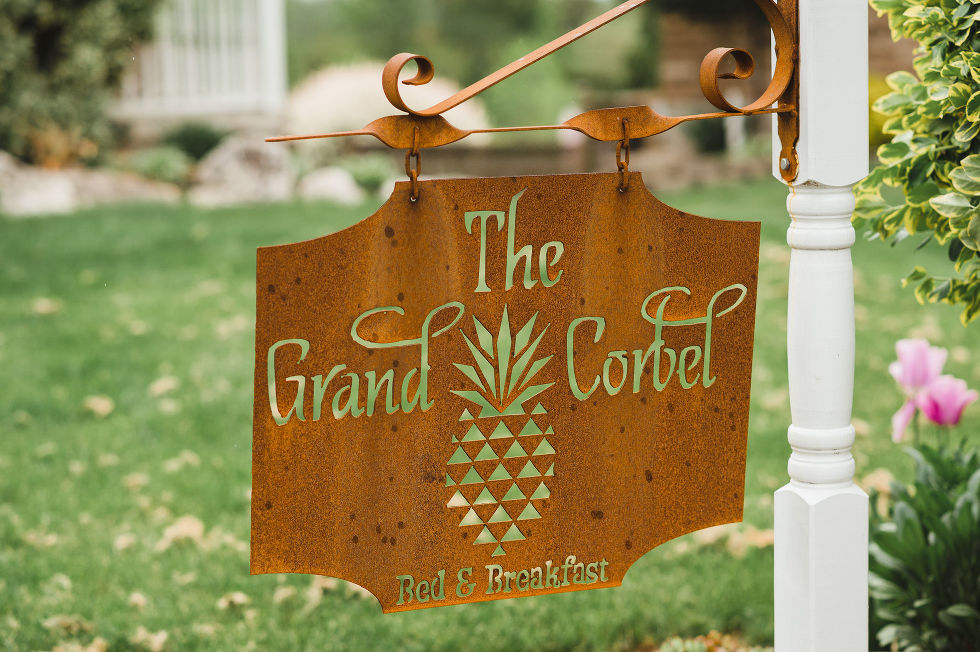 a brass sign for The Grand Corbet bed and breakfast with a pineapple design on it charming southern wedding at Ruthven Park National Historic Site