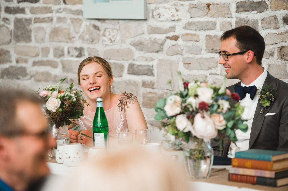 bride and groom laughing at their head table in front of an old stone wall during their charming southern style wedding at Ruthven National Historic Site near Hamilton