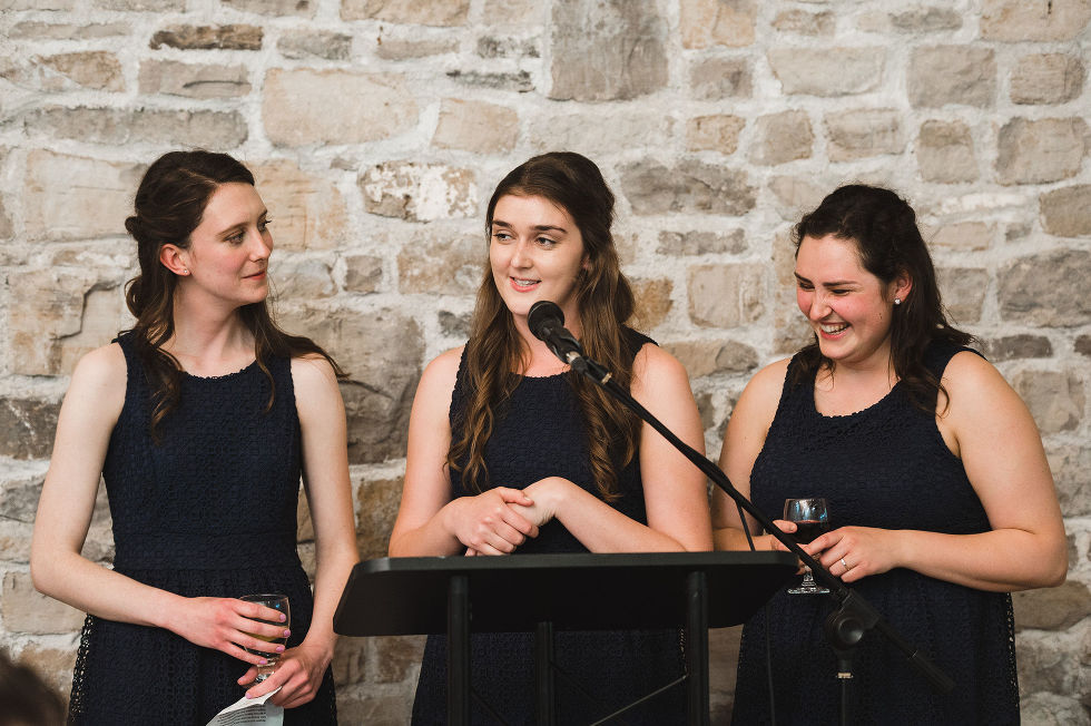 Three bridesmaids reading their speech in front of an old stone wall during a charming southern style wedding at Ruthven National Historic Site near Hamilton