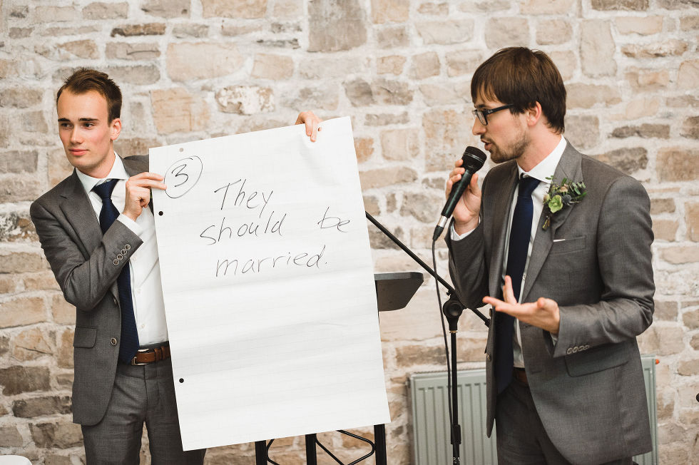 """A couple groomsmen holding up a large sheet of paper with """"They should be married"""" written on it as one of them reads into the microphone during a charming southern style wedding at Ruthven National Historic Site"""