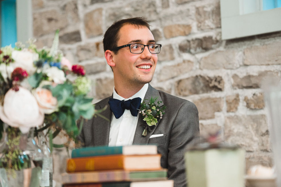 groom smiling at his head table in front of old stone wall with books and flowers on the table in front of him during his wedding at Ruthven National Historic Site