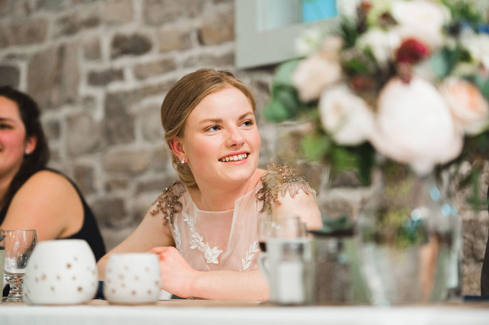bride smiling while sitting at the head table in front of old stone wall during speeches for her wedding at Ruthven National Historic Site