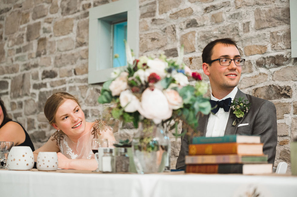 bride and groom smiling at their head table in front of old stone wall with books and flowers on the table in front of them during speeches at their wedding at Ruthven National Historic Site