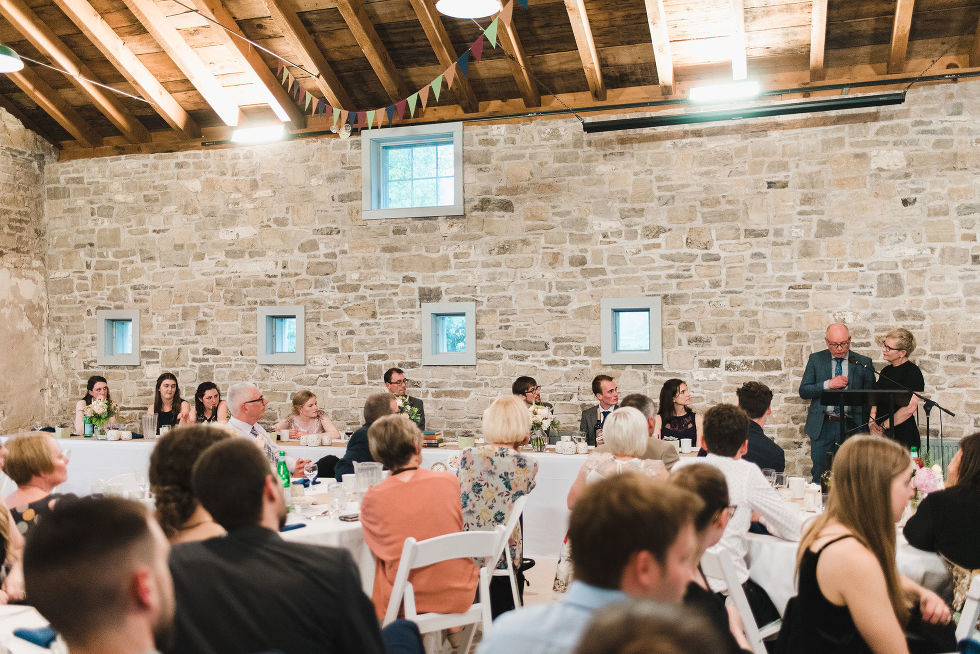 bride, groom, wedding party, and wedding guests all looking towards the podium and listening to speeches during a charming southern style wedding at Ruthven National Historic Site