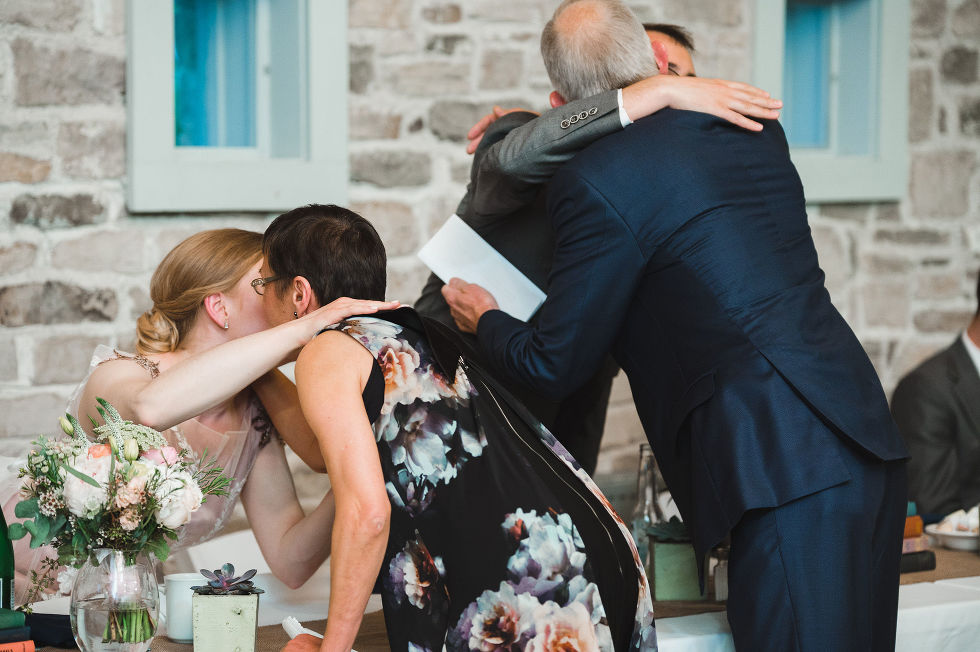 bride and groom getting up from their table to hug grooms parents after their speech during their charming southern style wedding at Ruthven National Historic Site near Hamilton