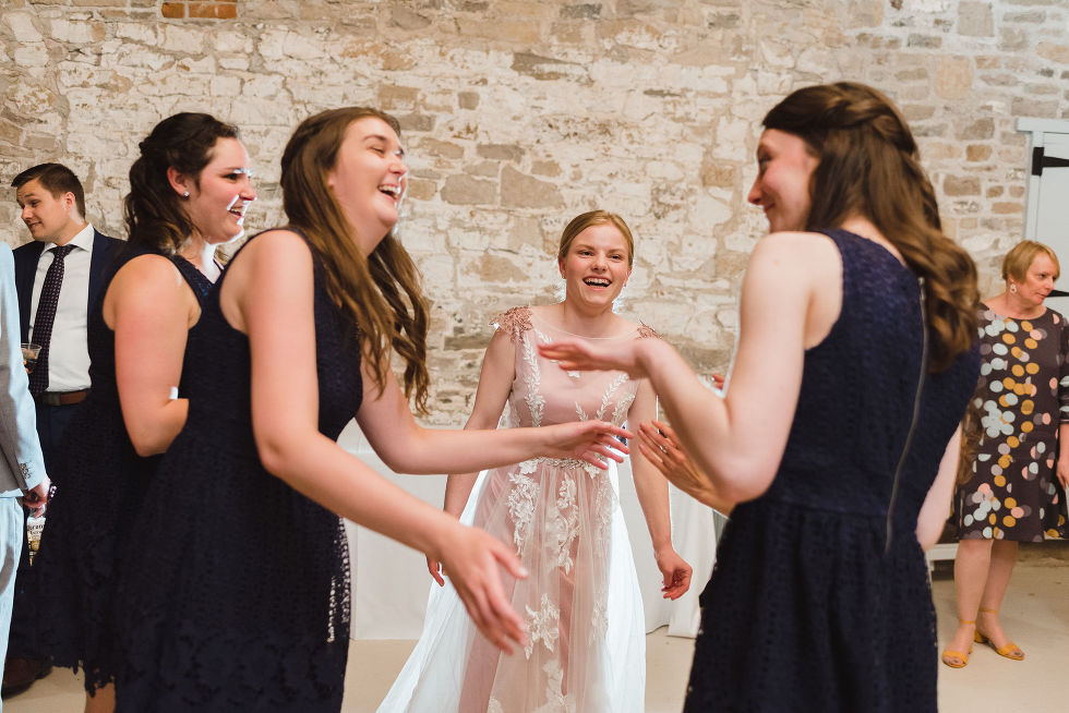 bride laughing and dancing with her bridesmaids during her charming southern style wedding at Ruthven National Historic Site near Hamilton