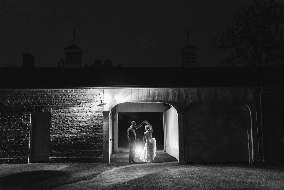 groom twirling his bride at dusk between an old stone building after their charming southern style wedding at Ruthven National Historic Site