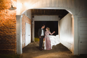 bride and groom standing together in a loving embrace at dusk between an old stone building after their charming southern style wedding at Ruthven National Historic Site