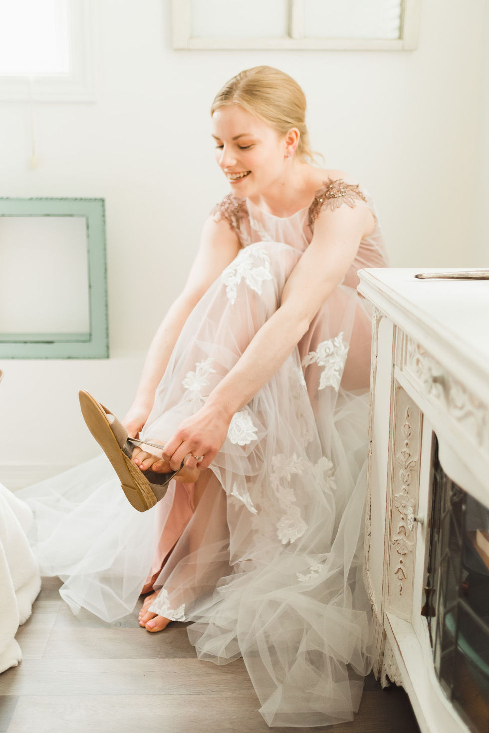 bride in her wedding dress seated while putting on her shoes before her charming southern style wedding at Ruthven Park National Historic Site
