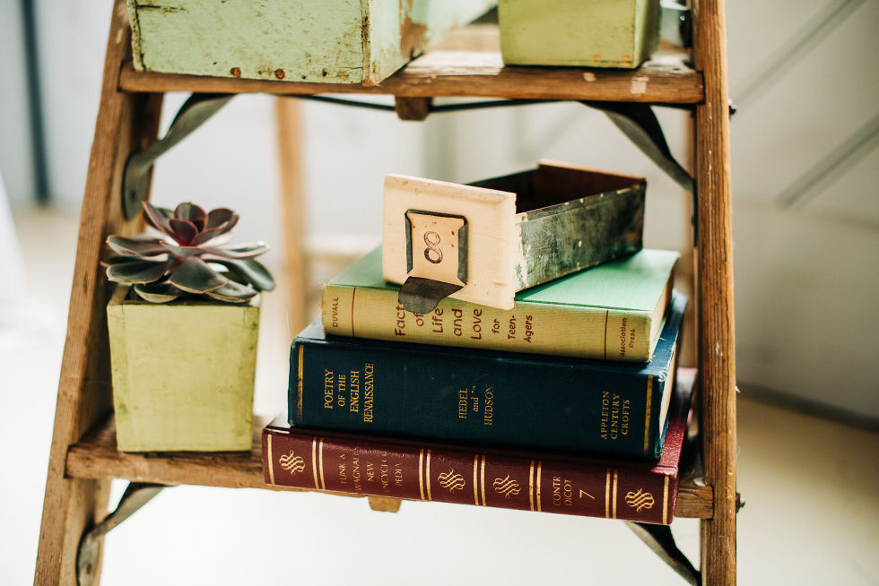 decorative vintage bookshelf with leather bound books set up for charming southern style wedding at Ruthven Park National Historic Site