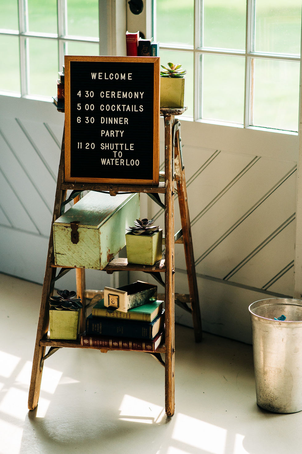 bookshelf with books and a welcome sign with a wedding day itinerary for the guests at Ruthven Park National Historic Site