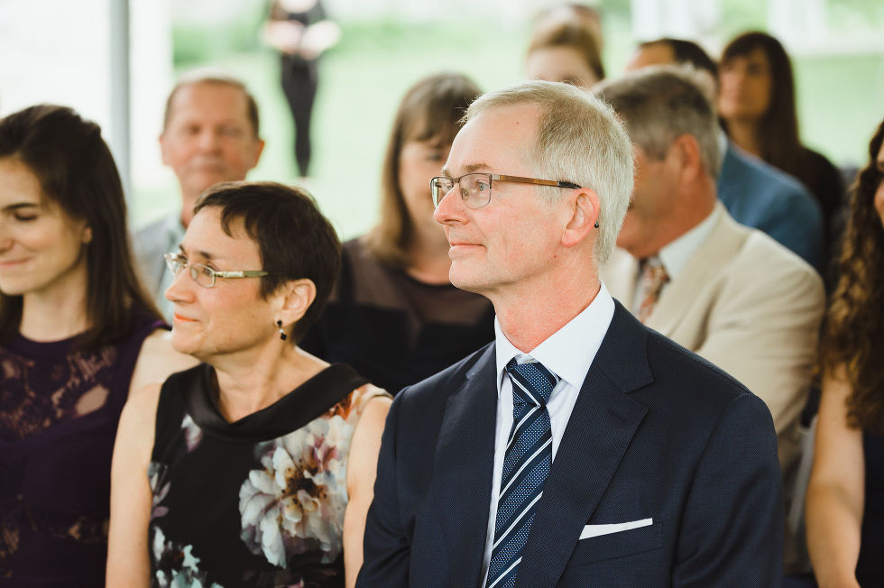 parents of the bride seated and watching their daughter get married at Ruthven Park National Historic Site near Hamilton Ontario