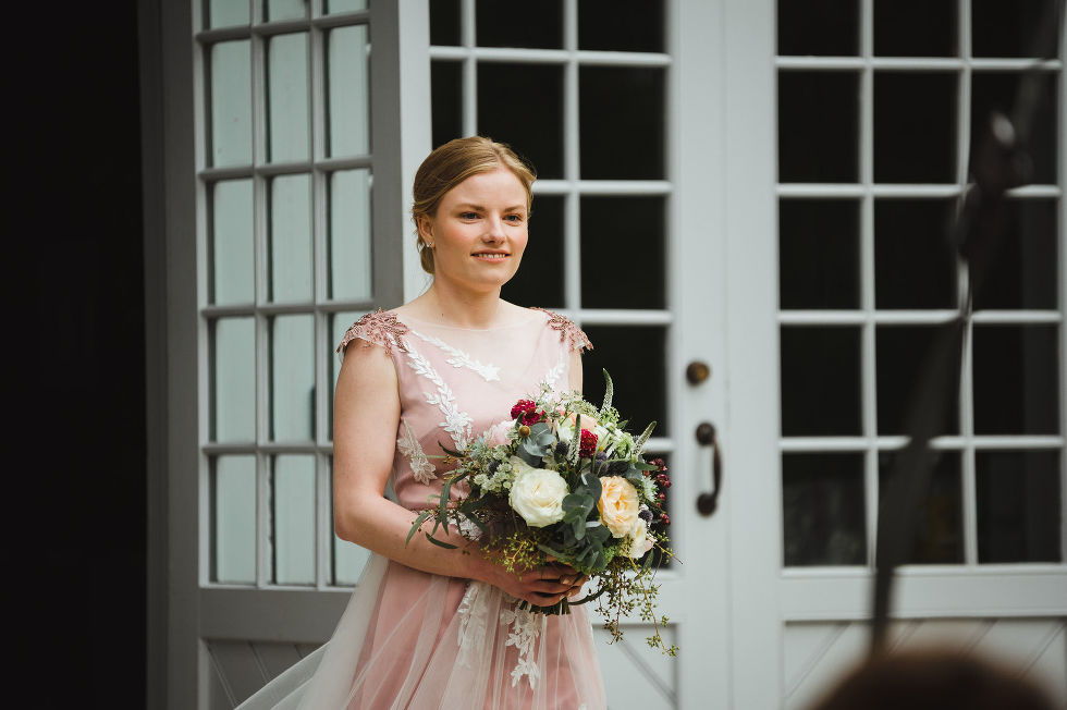bride holding floral bouquet beginning her walk down the aisle during her charming southern style wedding at ruthven national historic site