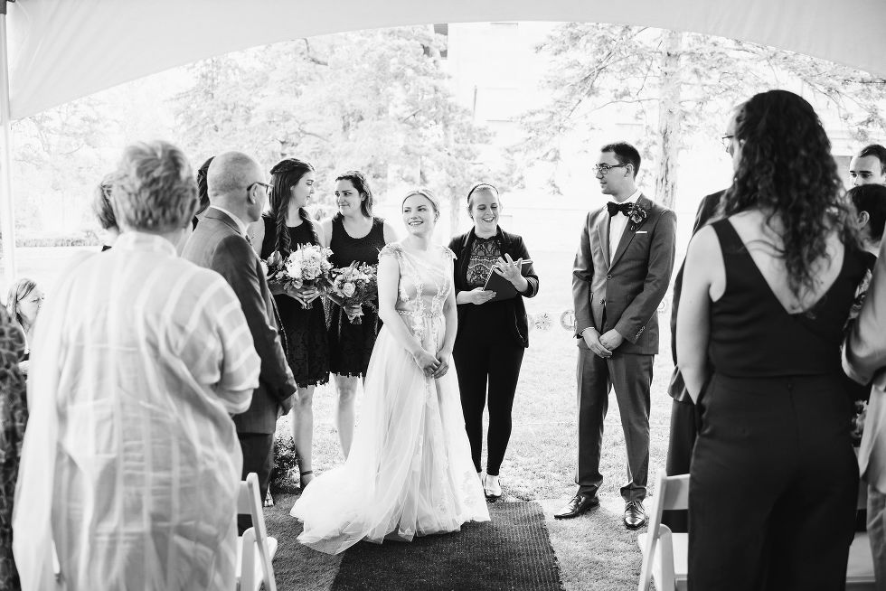 bride and groom stand before their wedding officiant as their guests and wedding party watch their charming southern style wedding at Ruthven national historic site