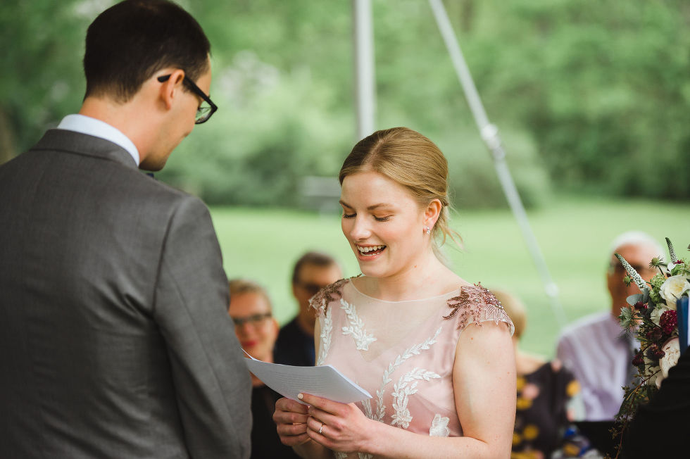 bride smiling at reading her vows to her groom during their charming southern style wedding ceremony at Ruthven national historic site