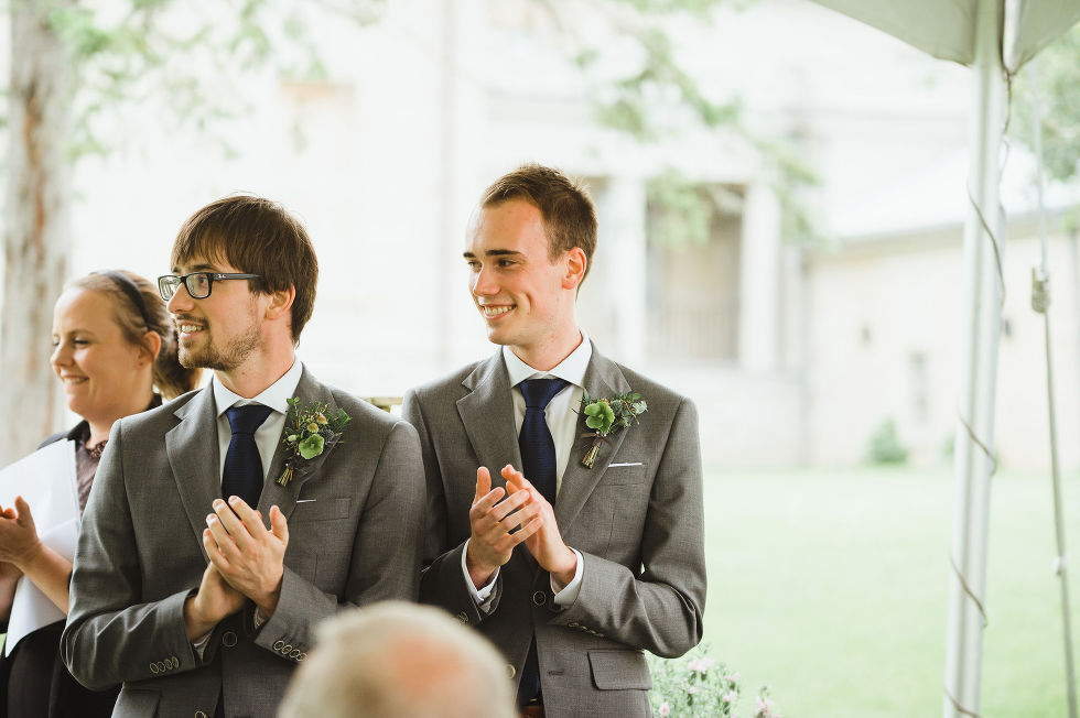 groomsmen in grey suits clapping as they watch a charming southern style wedding ceremony at Ruthven national historic site