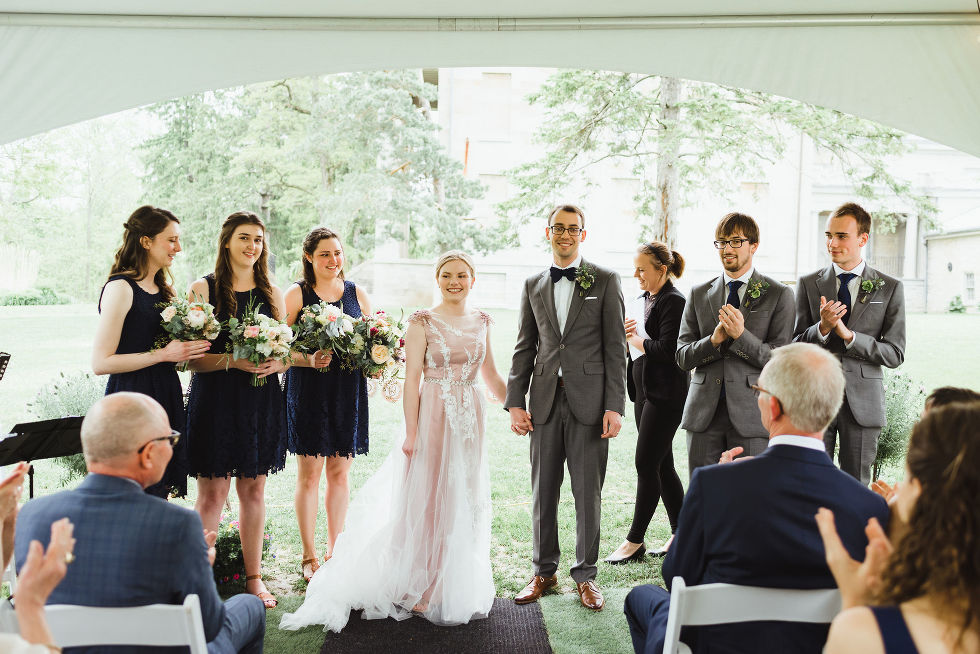 bride and groom holding hands as they stand between their wedding party and look out onto their wedding guests during their charming southern style ceremony at Ruthven National Historic Site near Hamilton