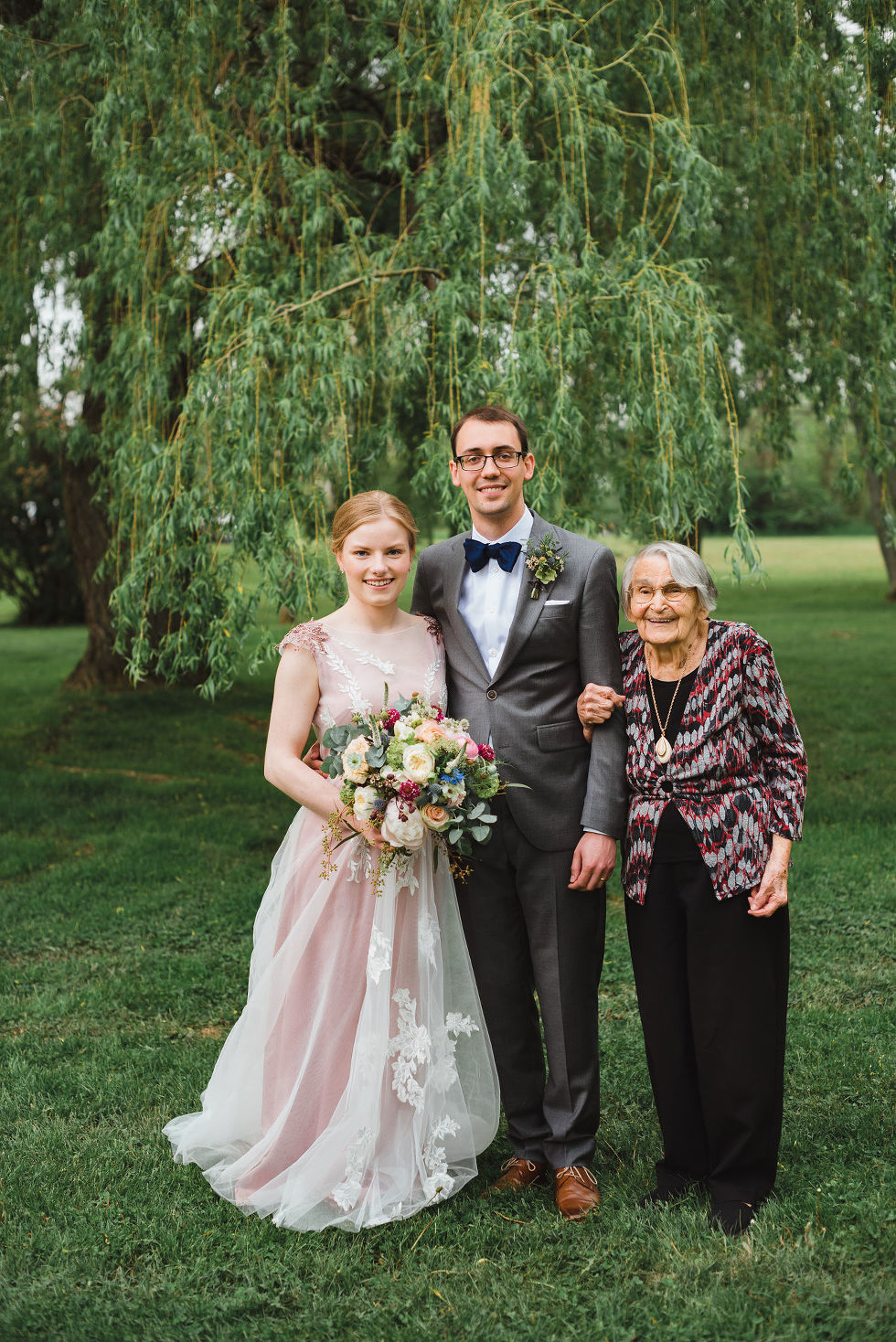 bride and groom stand with the grandmother underneath a willow tree during their southern style wedding at Ruthven National Historic Site near Hamilton