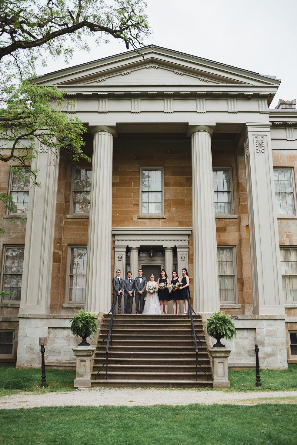bride and groom standing between their wedding party on stone steps between Greek stone columns of the Ruthven National Historic Site near Hamilton