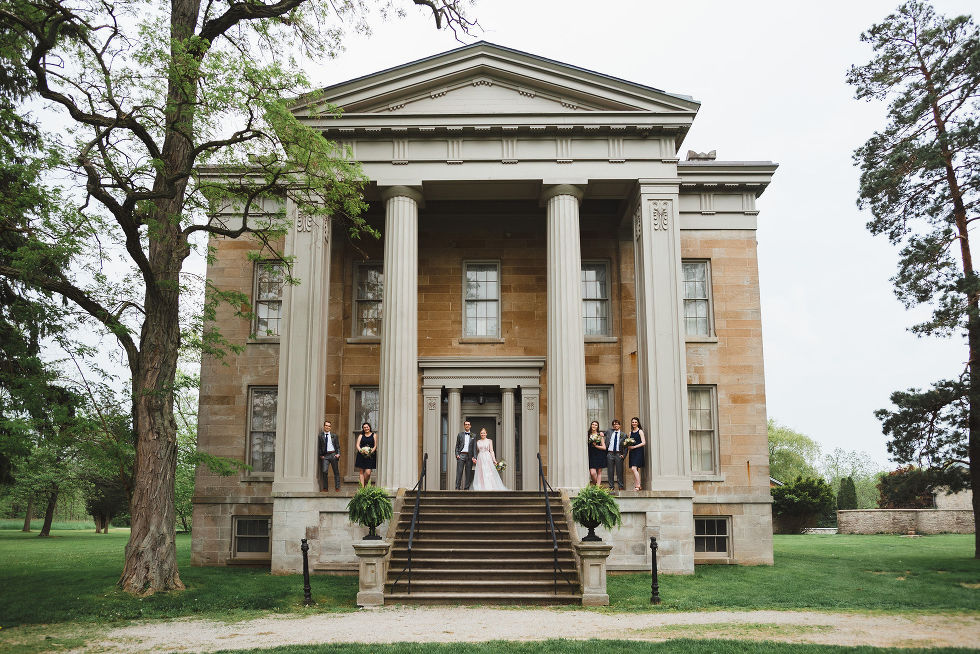 bride and groom standing between their wedding party on stone steps between Greek stone columns of the Ruthven National Historic Site after their charming southern style wedding near Hamilton