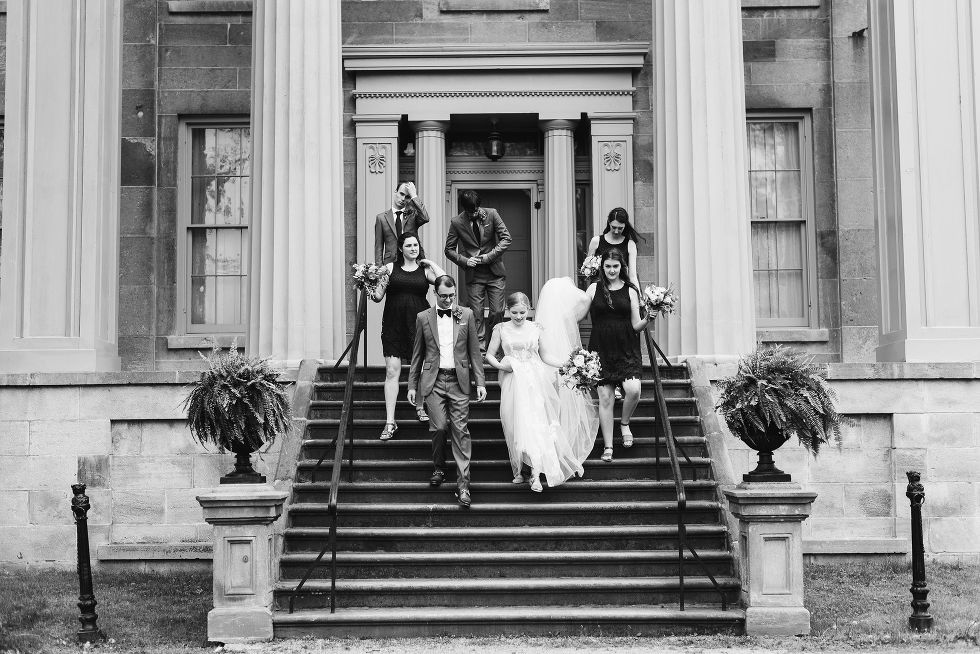 bride and groom walking down the steps with their wedding party between Greek stone columns of the Ruthven National Historic Site after their charming southern style wedding near Hamilton