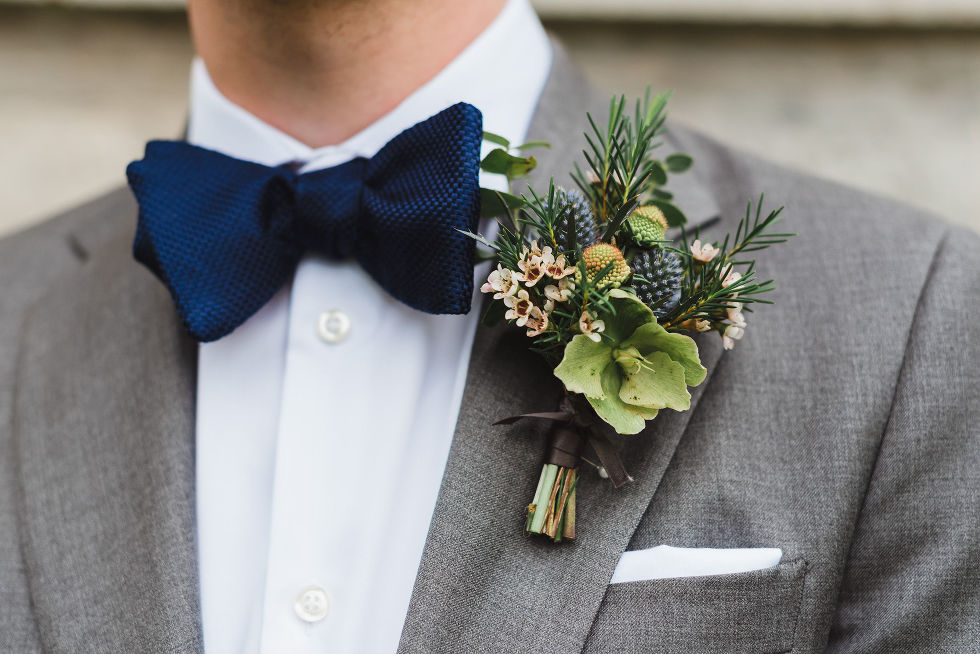 groom in a grey suit with a blue bowtie and a boutonniere during his charming southern style wedding at Ruthven National Historic Site