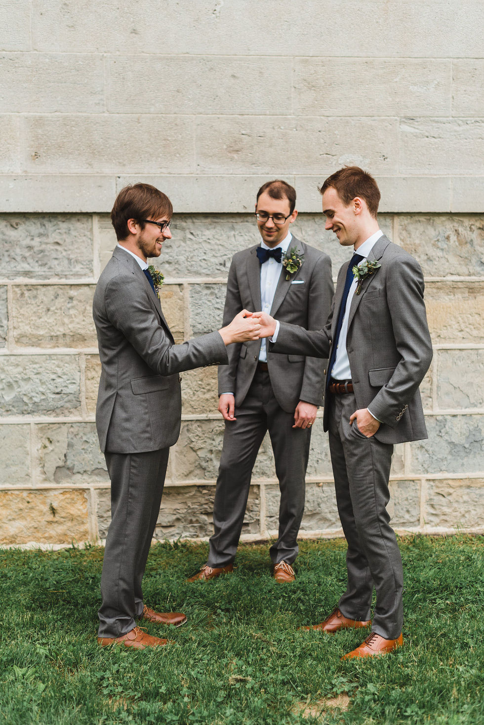 groom watching as his two groomsmen play thumb war in front of him during his charming southern style wedding at Ruthven National Historic Site