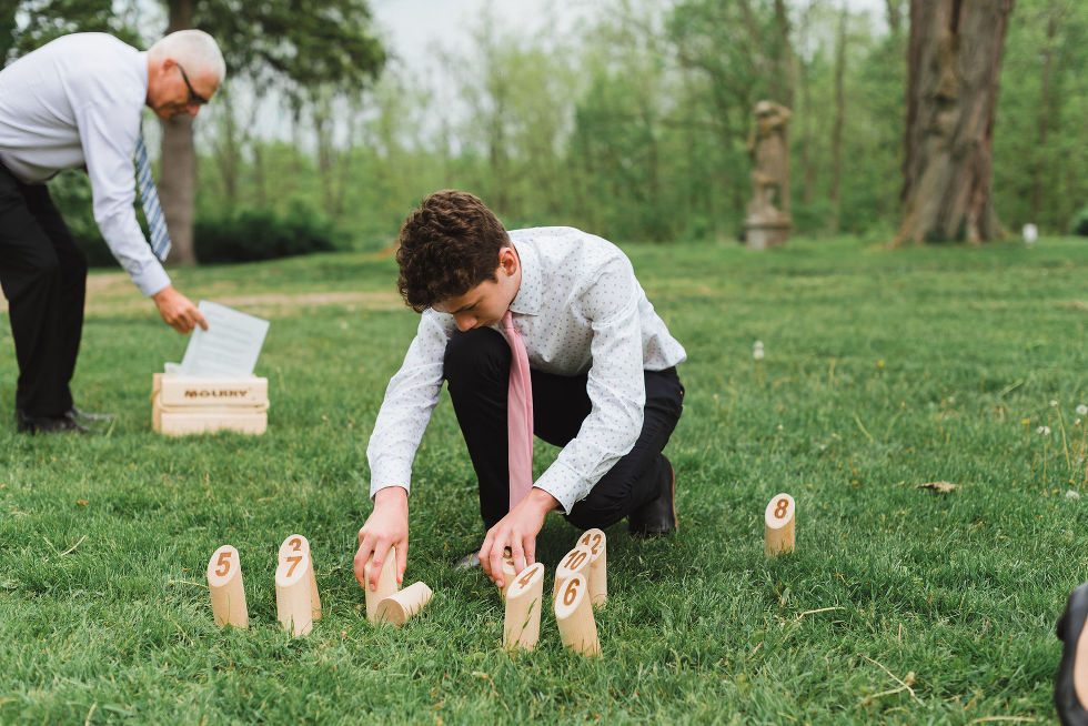 A couple of wedding guests setting up a game with wooden pegs with numbers on them on the lawn of the Ruthven National Historic Site during a charming southern style wedding near Hamilton