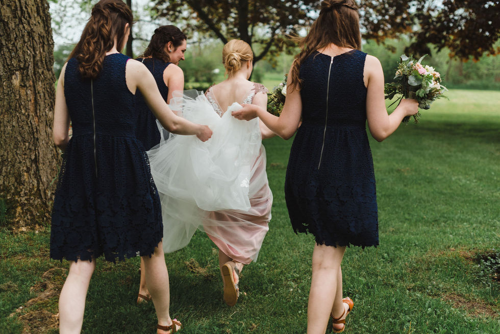 bride strolling on the lawn of the Ruthven National Historic Site while her three bridesmaids hold the back of the dress during her charming southern style wedding near Hamilton