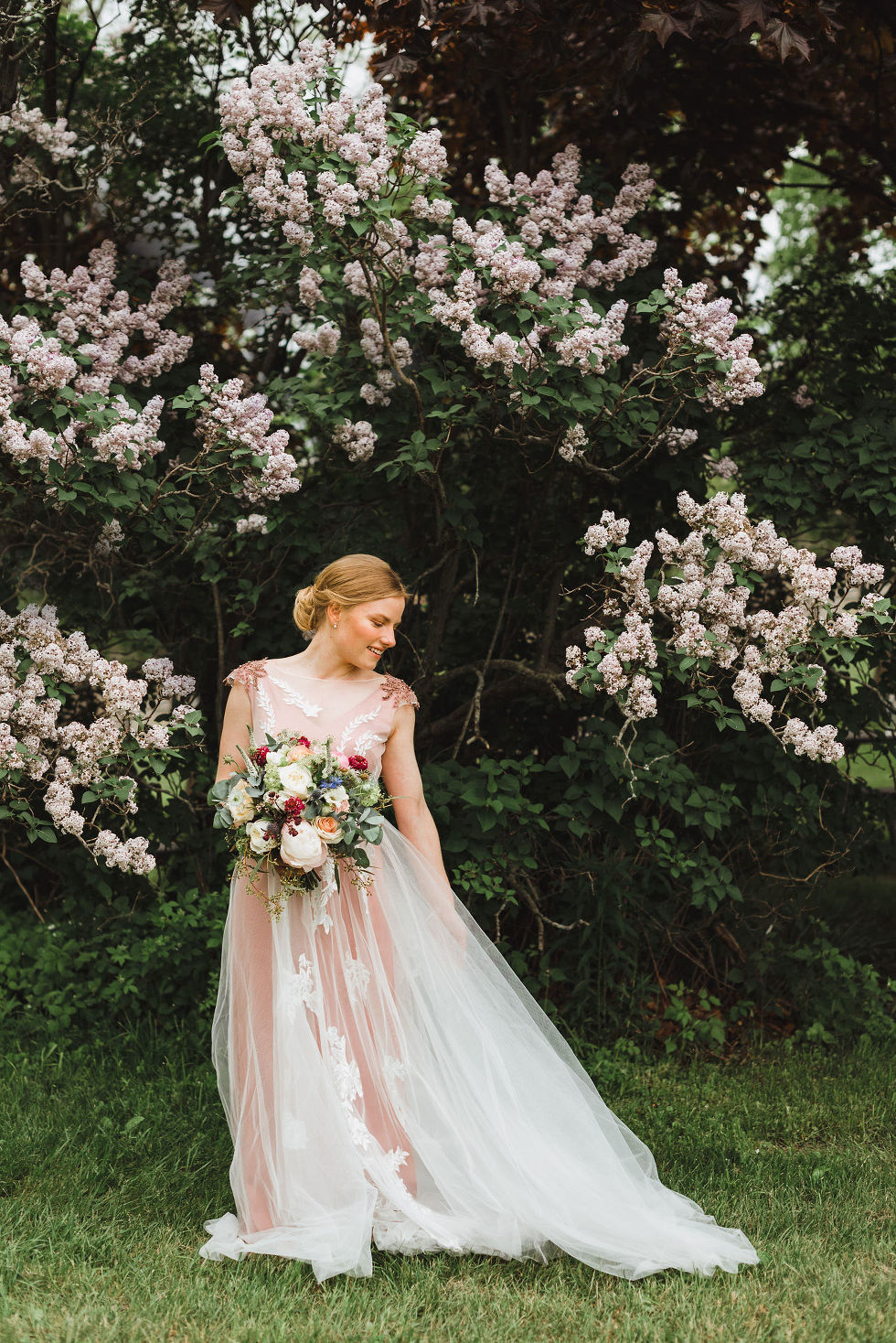 bride standing in front of lilac bushes holding a floral bouquet and looking down at her dress during her charming southern style wedding at Ruthven National Historic Site near Hamilton