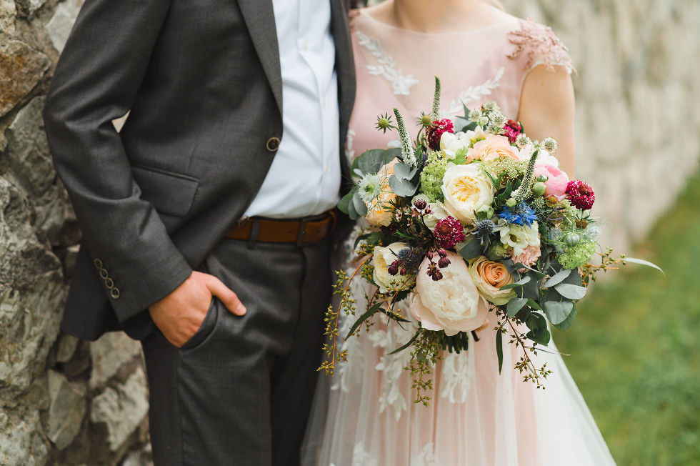 groom with his hand in his pocket leans against old stone wall while his bride stands next to him holding a colourful bouquet of flowers during their charming southern style wedding at Ruthven National Historic Site near Hamilton