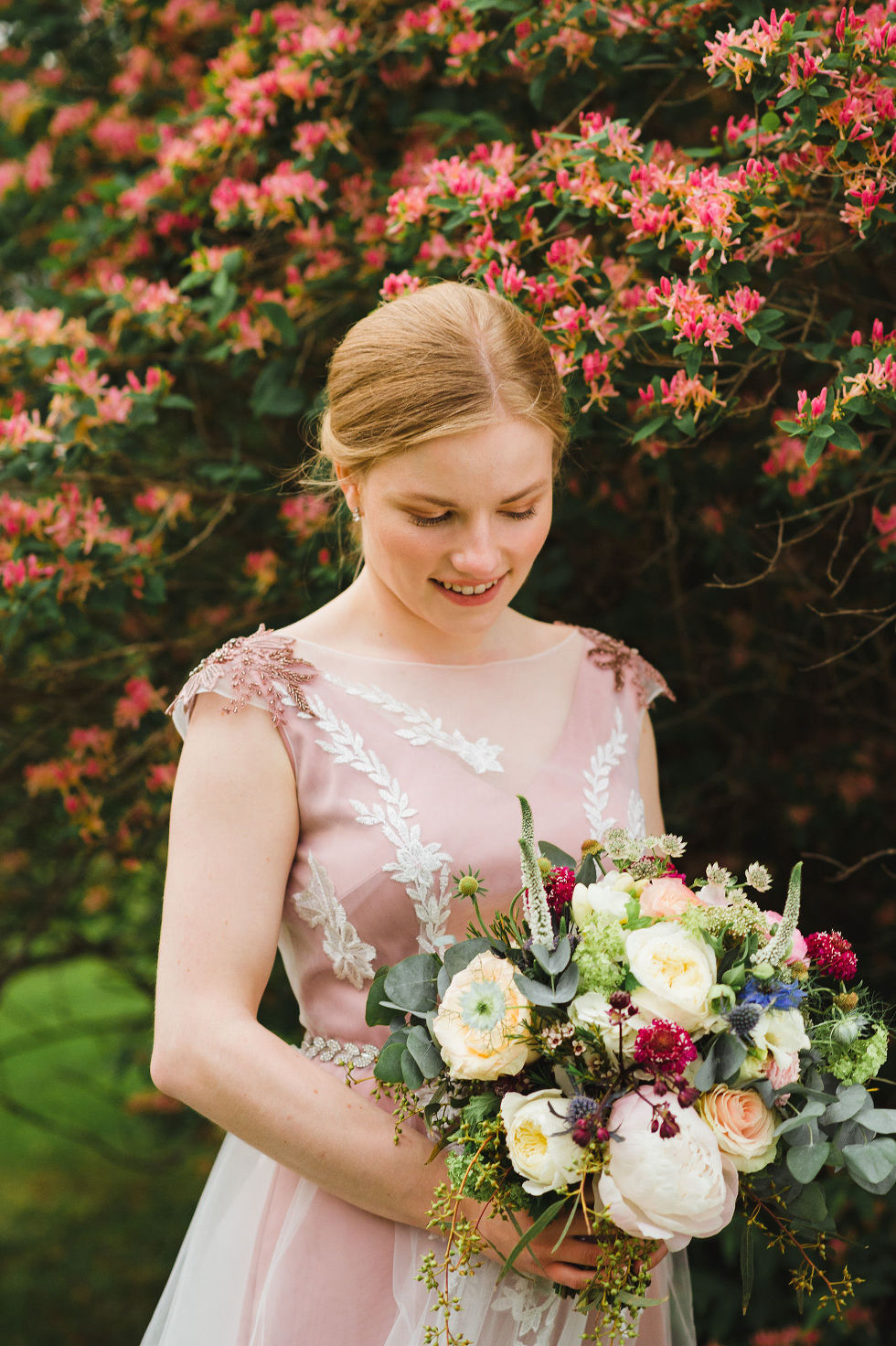 bride standing in front of a wall of colourful flowers holding a bouquet during her charming southern style wedding at Ruthven National Historic Site near Hamilton