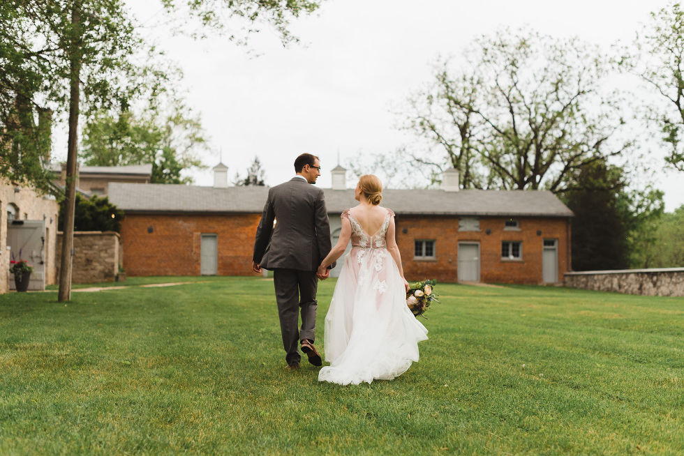 bride and groom stroll hand in hand across the lawns of the Ruthven National Historic Site during their charming southern style wedding