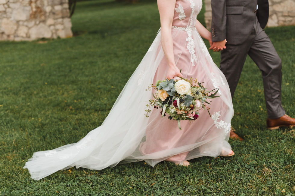 bride holding colourful bouquet of flowers as she and her groom stroll hand in hand across the lawns of the Ruthven National Historic Site during their harming southern style wedding