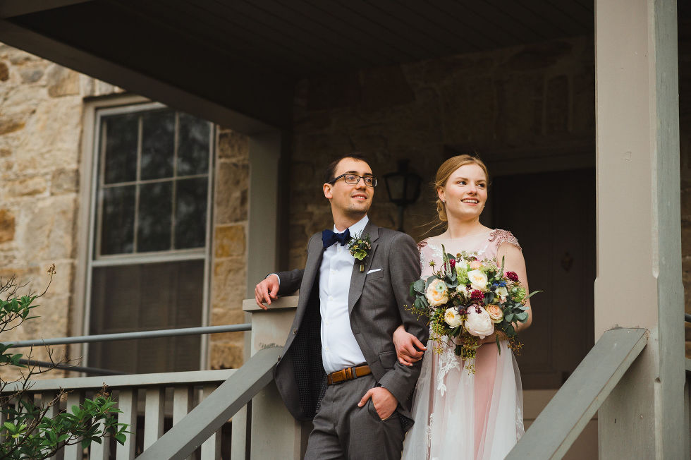 bride holding a colourful floral bouquet and her other arm linked with her grooms during their charming southern style wedding at Ruthven National Historic Site near Hamilton