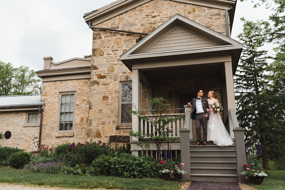 bride holding a colourful bouquet and her other arm linked with her grooms during their charming southern style wedding at Ruthven National Historic Site near Hamilton