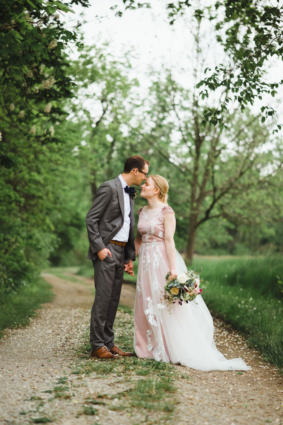 groom kissing his bride on the forehead as they walk along a forested path during their charming southern style wedding at Ruthven National Historic Site near Hamilton