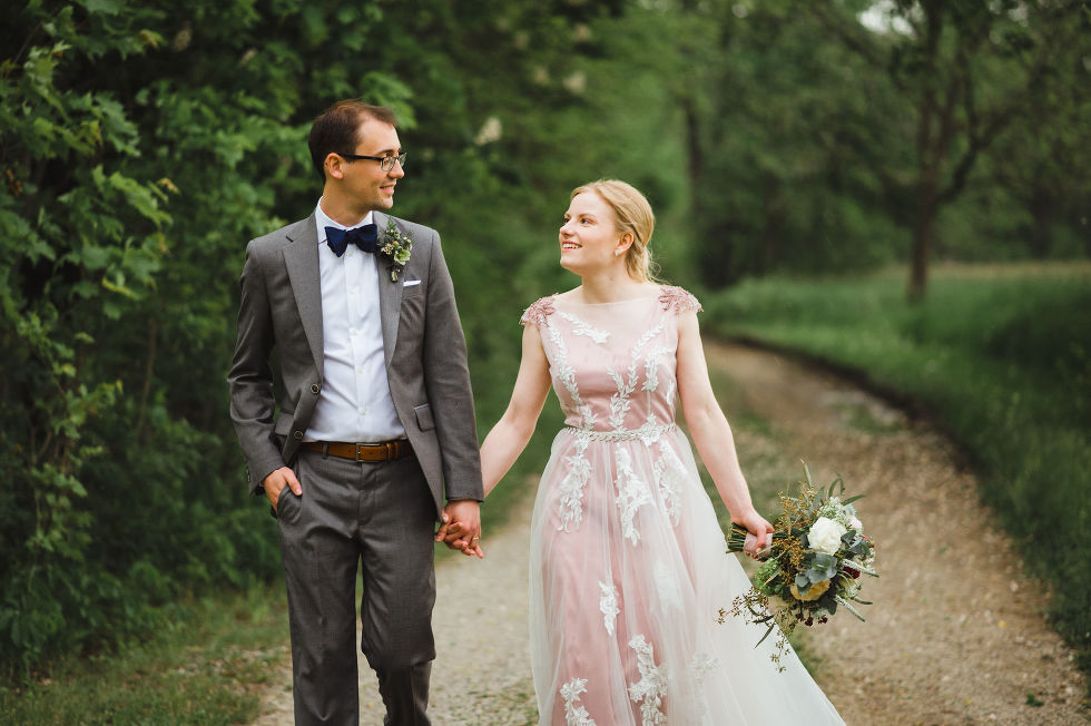 bride and groom holding hands as they walk along a forested path during their charming southern style wedding at Ruthven National Historic Site near Hamilton