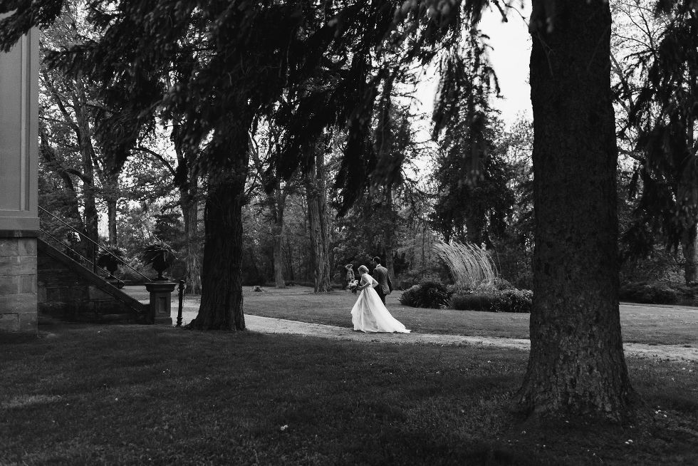 bride and groom walk along a forested path leading to a stone building during their charming southern style wedding at Ruthven National Historic Site near Hamilton