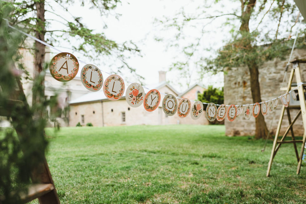 """Paper circles strung up saying """"ALL YOU NEED IS LOVE"""" outside Ruthven Park National Historic Site during a charming southern style wedding"""