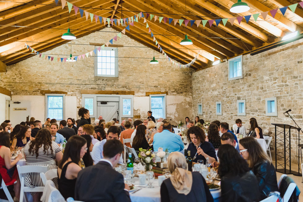 tables filled with wedding guests inside large stone reception hall during a charming southern style wedding at Ruthven National Historic Site near Hamilton