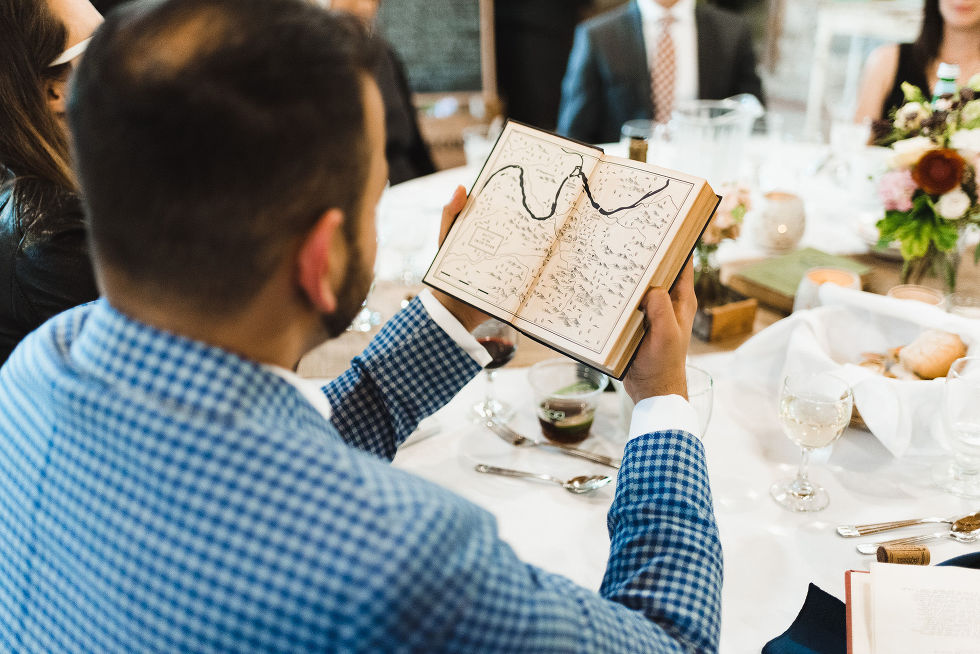 a wedding guest seated at his table and opening a book to look inside during a charming southern style wedding at Ruthven national historic site
