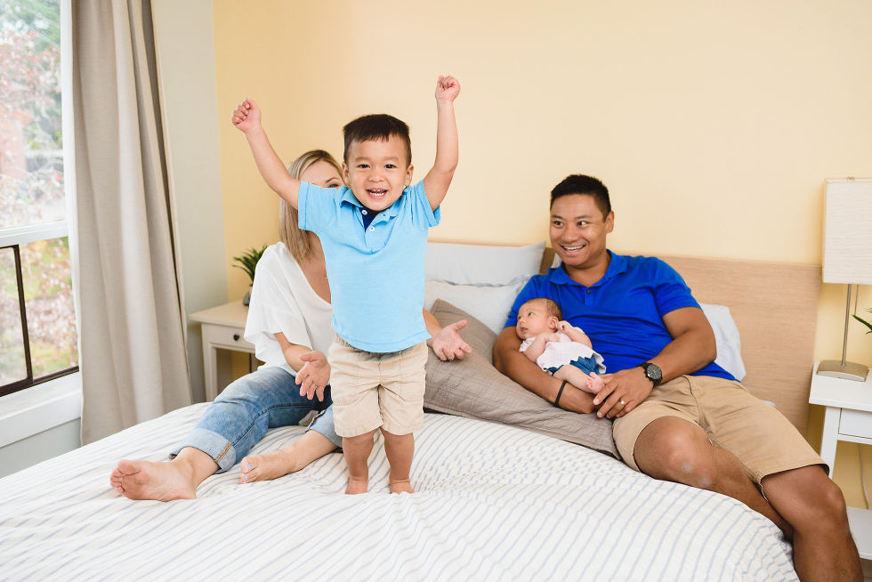 Husband and wife laying down on their bed with a newborn in dads arms and a toddler standing on the bed with his arms in the air Toronto family photography